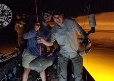 two-guys-on-boat-with-stingray-caught-Bowfishing-for-Bachelor-Party-Weekend-Trip-